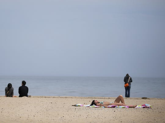 Valerie Mikels of Rochester catches some sun at Ontario Beach Park on Sunday.