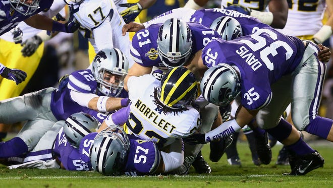 Michigan Wolverines wide receiver Dennis Norfleet is tackled by the Kansas State Wildcats defense during the Buffalo Wild Wings Bowl at Sun Devil Stadium.