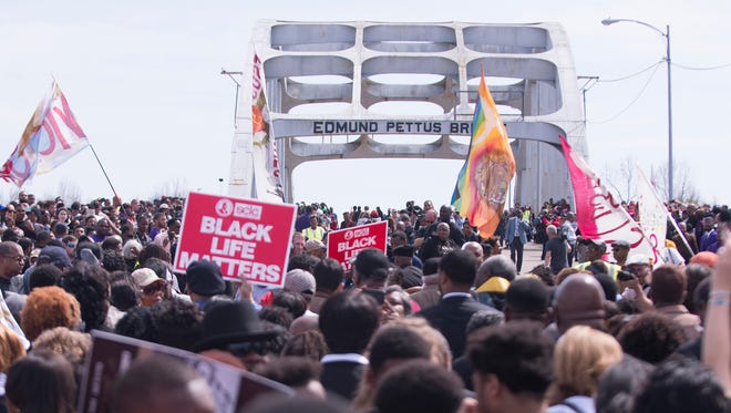 People march across the Edmund Pettus Bridge to commemorate the 50th anniversary of Bloody Sunday in Selma, Ala., on Sunday, March 8, 2015.