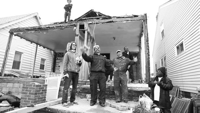 """Artist Ryan Mendoza (standing left) and crew demolishing """"The White House"""" in Detroit in 2015."""