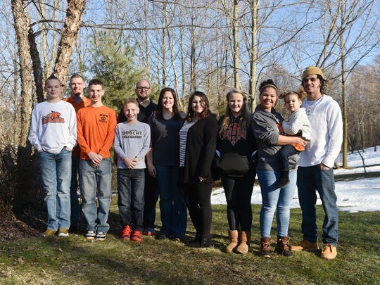 The Burnham family stands for a portrait outside their temporary home in Hellam Township. From left to right: Jackson, 13; Blake, 19; Anthony, 13; Cassius, 11; parents Jesse and Crystal; Corinne, 19; Eve, 11; Camryn, 18, holding her niece Ophelia, 2; and Robert, 25, who is Ophelia's father. Every child Crystal and Jesse Burnham have fostered has either been sent back to his or her birth family or adopted by the Burnhams, who have six adopted children, most of whom still live with them.