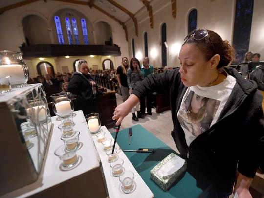 Yolanda Shaw lights a candle for her sister Ruby Mercado  who was shot and killed on Aug. 29. Shaw joined others in the Trinity United Church of Christ, during the 30th annual Crime Victim' Rights March and Candlelight Vigil.