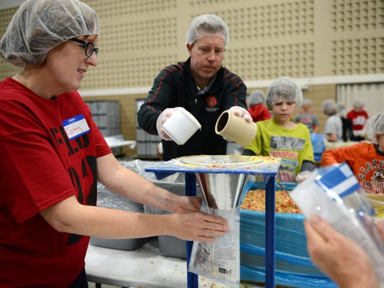 From left, Judy Emmett, Ben Urcavich and his two sons, Noah, 8, and Jordan, 6, work as a team to measure and bag meals at the Feed My Starving Children MobilePack event Tuesday at Green Bay Community Church in Howard.