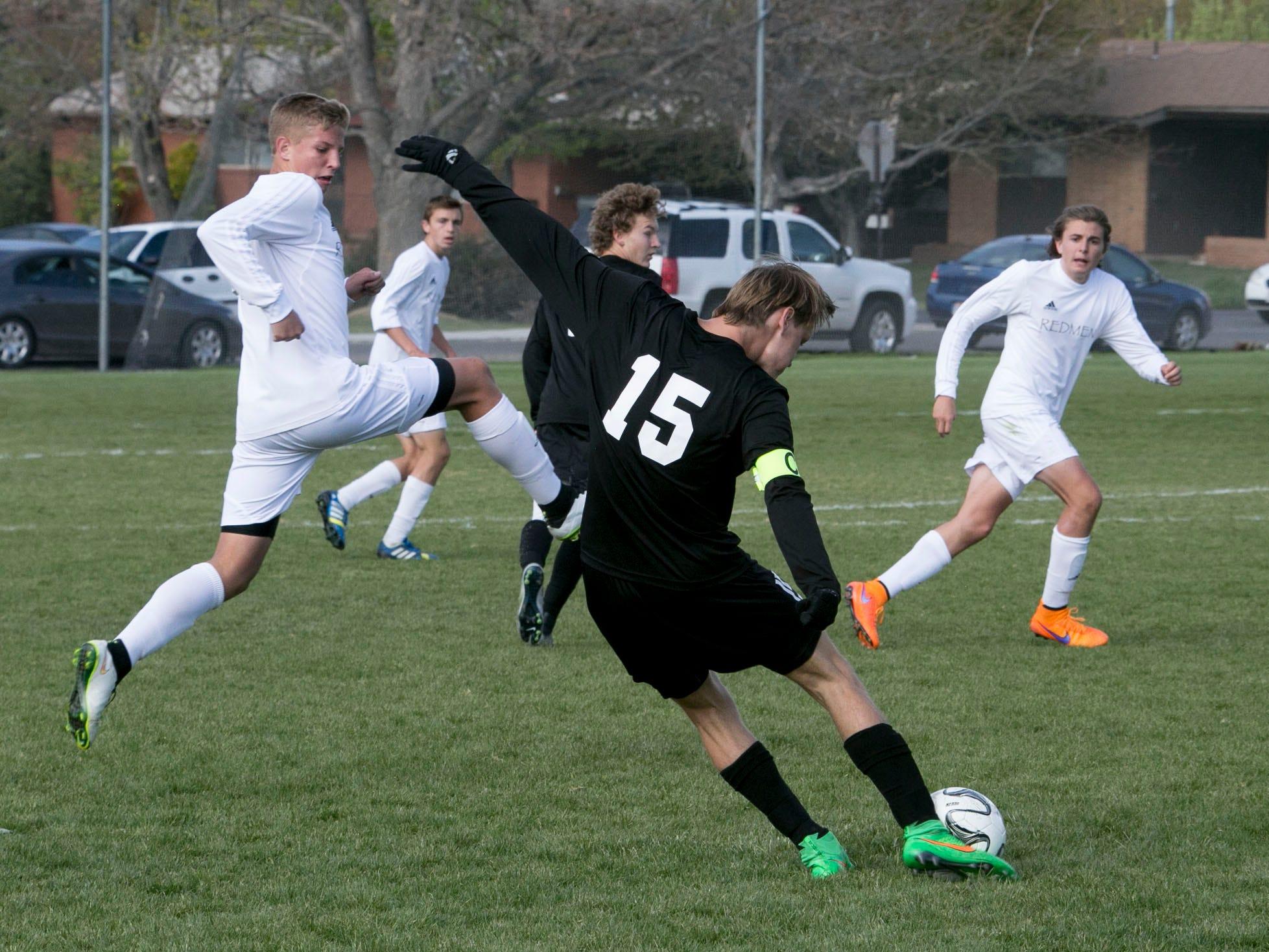 Desert Hills' Blake Evans kicks the ball over Cedar High's defense Friday.