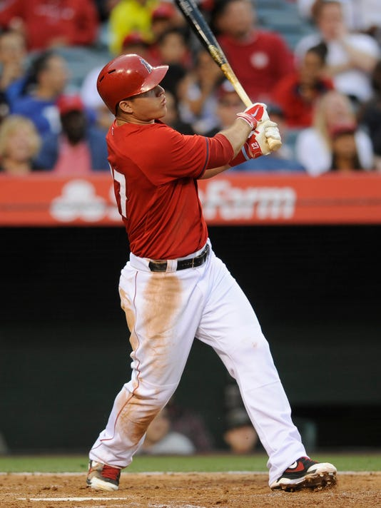 Los Angeles Angels center fielder Mike Trout follows through on a solo home run during the second inning of an exhibition baseball game against the Los Angeles Dodgers in Anaheim, Calif., Saturday, March 29, 2014. (AP Photo/Kelvin Kuo)