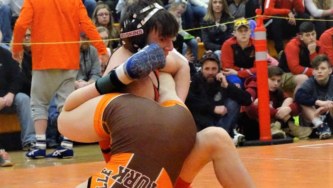 Coshocton's Lucian Brink wrestles Nelsonville-York's Collin Yinger in the 106-pound final during Saturday's Division III district meet. Brink won the district title with a 2-0 decision.