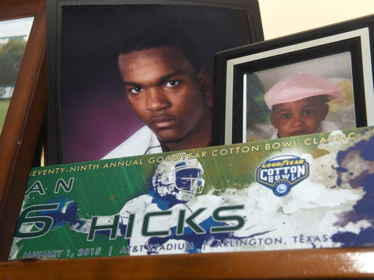 Photographs remain of Mylan Hicks in the living room of his parents' Detroit home.