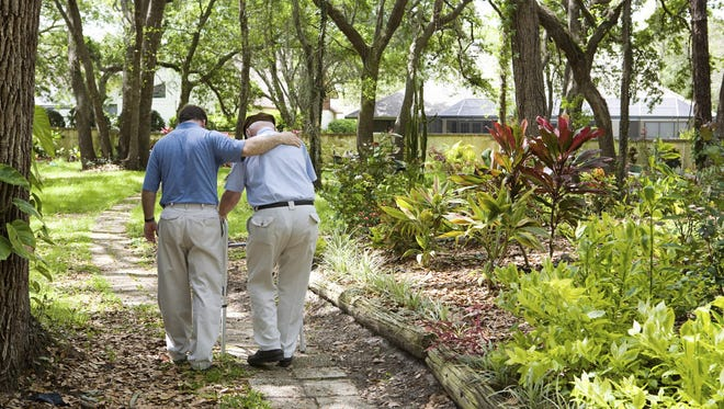 An adult son walks with his senior father in the park.