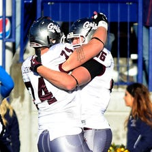 John Schmaing, 74, celebrates a touchdown with Montana teammate Clay Pierson during last season's Cat-Griz game. TRIBUNE PHOTO/RION SANDERS