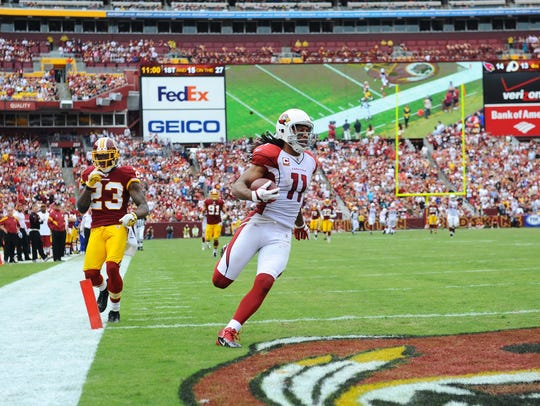 Larry Fitzgerald carries the ball in for a touchdown after a catch as Redskins cornerback DeAngelo Hall trails behind on Sept. 18, 2011.