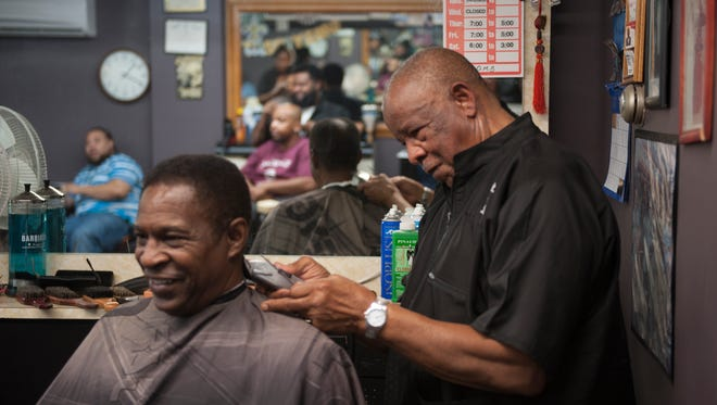 Rev. Paul Bryant Sr. cuts the hair of Roger Williams at Bryant's  Barber Shop in Clayton. Bryant opened the shop in 1967. His son, daughter and grandson continue the tradition.