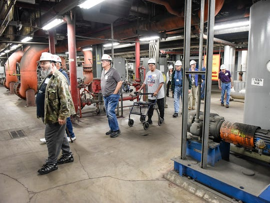 In this June 2017 file photos veterans from the St. Cloud VA Health Care System walk along pipe alley that connect the three generating units during a tour of Xcel Energy's Sherco coal-fired plant in Becker.