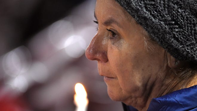 A woman listens during a vigil for shooting victims on Thursday, Dec. 3, 2015, at San Manuel Stadium in San Bernardino, Calif. A husband and wife opened fire on a holiday banquet, killing multiple people on Wednesday. Hours later, the couple died in a shootout with police. (AP Photo/Mark J. Terrill)