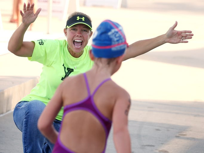 Tanya Devlieger yells encouragement to a runner on Sunday. On Sunday, July 13, 2014, 250 children, ages 5-15, plus hundreds of supporters, gathered at the FSU Morcom Aquatic Center, to take part in the Splash & Dash youth aquathlon. This non-competitive swim-run event is put on by USA Triathlon (USAT), but is hosted by the 2014 Tallahassee Youth Triathlon Series (TYTS). Participants swam laps and ran 1/2 mile.