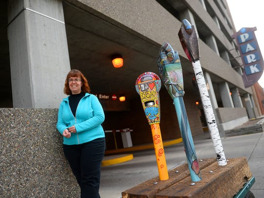 Joan Redeen of the Great Falls Business Improvement District stands with four painted parking meters in front of the 4th Street North parking structure.  Joan uses these meters as an example of a project she is working on to decorate decomissioned analogue meters that will be planted in front of the 4th street structure as an interactive art installation.  The money collected in the meters with help fund future art projects downtown.