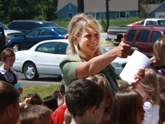Chris Parker, principal of Harrison Elementary, gives her students a thumbs-up while gathering them for a first-day group picture in front of the school in 2009.