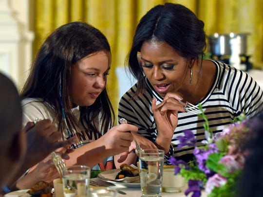 First lady Michelle Obama and a student look over their plates as they eat lunch in the East Room of the White House on Oct. 14 following the annual fall harvest of the White House Kitchen Garden in Washington.