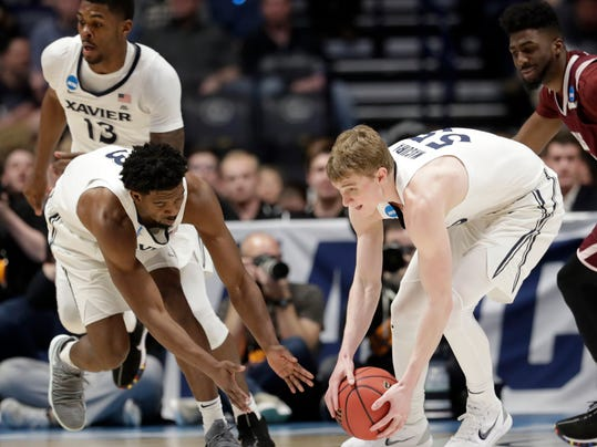 Xavier guards J.P. Macura (55) guard Quentin Goodin (3) chase down a loose ball in the second half of a first-round game of the NCAA college basketball tournament in Nashville, Tenn., Friday, March 16, 2018. (AP Photo/Mark Humphrey)