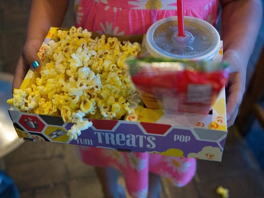 "Isabella Osburn, 7, holds a tray of movie treats, before going to see ""Ratchet & Clank"" during Allen Theatres' 2017 Summer Kids Series, Tuesday, June 13, 2017."