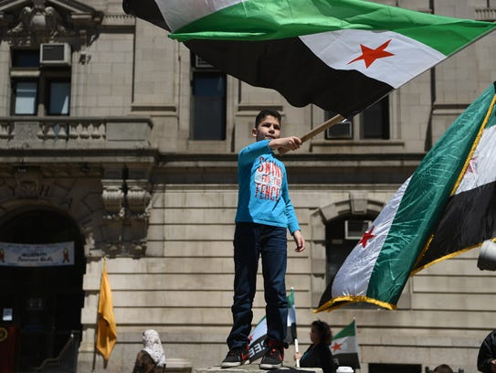 Walid Alkabouni, 9, of Elmwood Park proudly waves a