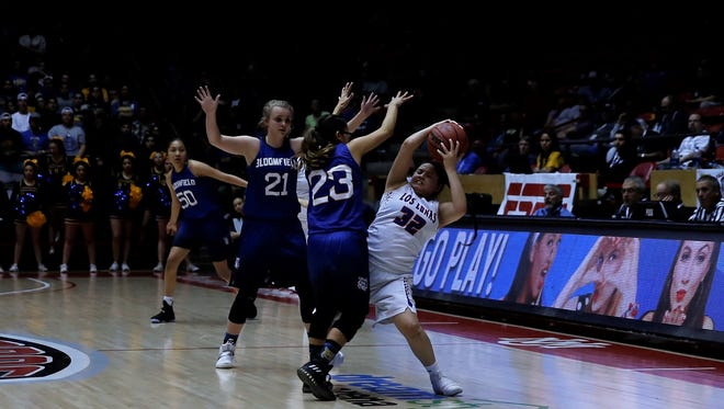 Bloomfield's Halle Payne (21) and Kimberly Morgan (23) trap Los Lunas' Amber Trujillo in the outer lane during Friday's 5A state championship game in Albuquerque.