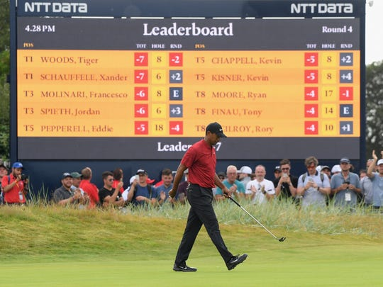 Tiger Woods tops the British Open leaderboard while playing the No. 9 hole Sunday.