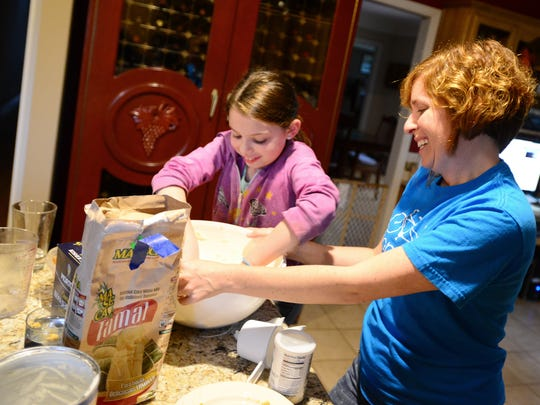 Skylar Haas, 10, and her mother, Ericka Haas, make tamales at their NE Salem home on Friday, Nov. 28, 2014. Her family opted to stay home and spend time together instead of shopping on Black Friday.