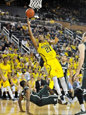 Michigan State's Lourawls Nairn, Jr., tries to draw a charge by Michigan's Zak Irvin (21) in the second half of Tuesday night's game.