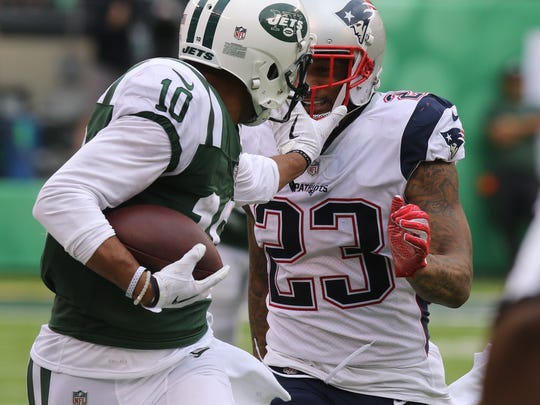 Jermaine Kearse of the Jets stiff arms Patrick Chung of the Patriots after a catch.