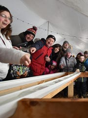 Fans cheer Alice Gillam's minnow as it scoots along in the minnow races at lest year's Fish Creek Winter Festival.