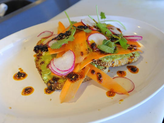 Avocado toast at O.W.L. is a winner: grilled sesame bread topped with mashed avocado and hard-cooked egg, accented with thinly sliced radishes and carrot strips and a frill or two of cilantro.