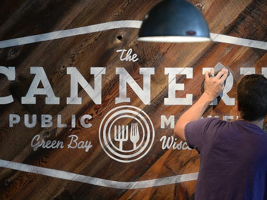 Brian Berggren of Wild Blue Technologies sands a sign with the logo of The Cannery on Broadway. The staff has been busy testing recipes and getting supplies ready for the market's August opening.