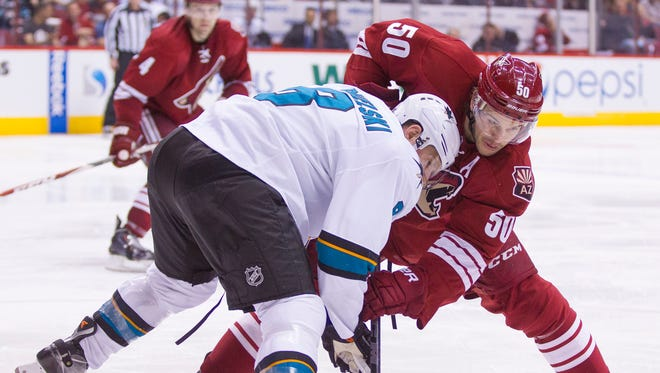 Sharks' Joe Pavelski (8) and Coyotes' Antoine Vermette (50) face-off in the third period at Gila River Arena in Glendale on Feb. 13, 2015.