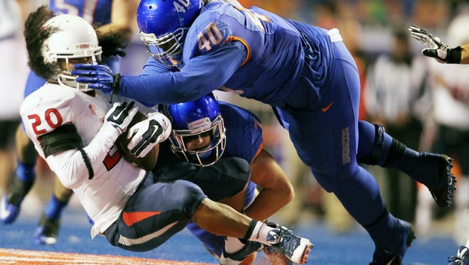 Boise State defensive tackle Armand Nance (40) and Boise State linebacker Joe Martarano bring down Fresno State running back Josh Quezada (20) during the Mountain West Championship game on Saturday Dec. 6, 2014.