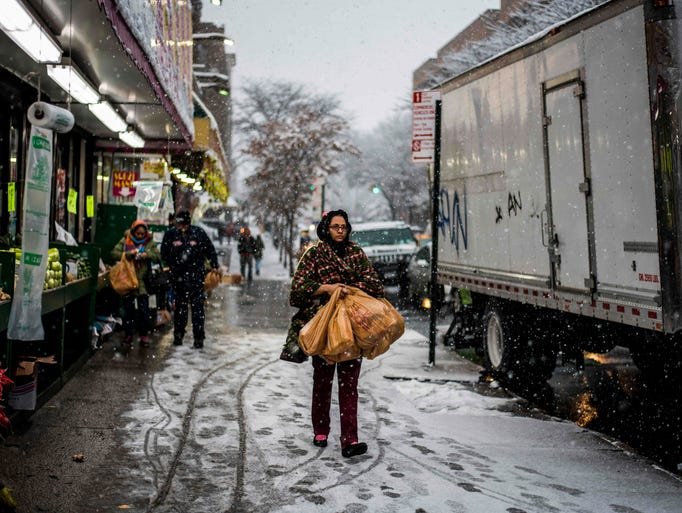 A woman makes her way carrying grocery bags during