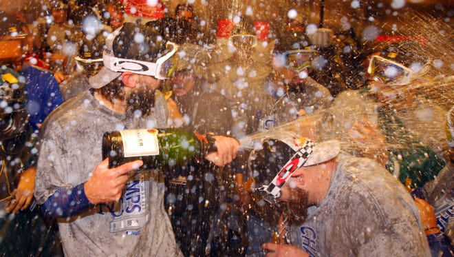 The Royals celebrate with champagne in the clubhouse after defeating the Mets.
