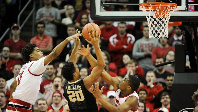 Louisville Cardinals forward Raymond Spalding (13) and guard Donovan Mitchell (45) pressure the shot of Wake Forest Demon Deacons forward John Collins (20) during the second half at KFC Yum! Center.
