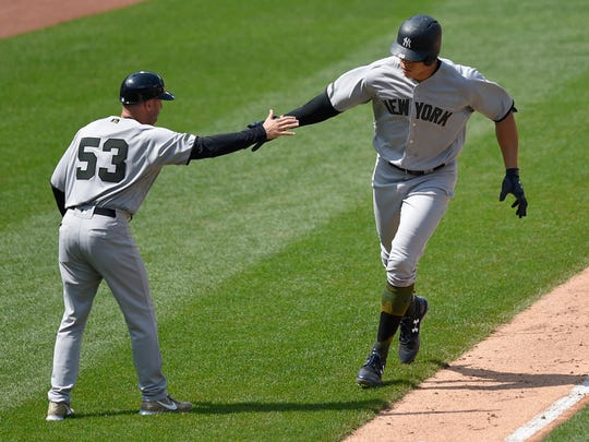 New York Yankees' Aaron Judge, right, is greeted by third base coach Joe Espada (53) after he rounded third after his home run during the seventh inning of a baseball game against the Baltimore Orioles, Monday, May 29, 2017, in Baltimore.