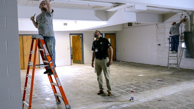 Justin Peterson, middle, Anderson School District 4 instructional coach, looks at painters in the STEAM lab, one of several improvements happening at Riverside Middle School in Pendleton three weeks before students return August 20.