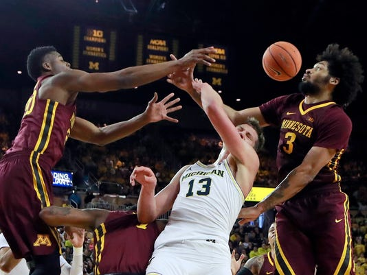 Minnesota forwards Davonte Fitzgerald, left, and Jordan Murphy, right, battle for a rebound with Michigan forward Moritz Wagner (13) during the second half of an NCAA college basketball game, Saturday, Feb. 3, 2018, in Ann Arbor, Mich. (AP Photo/Carlos Osorio)