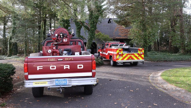 Fire department vehicles are parked in front of a residence on Bunting Lane Monday, where an early-morning fire displaced a family.