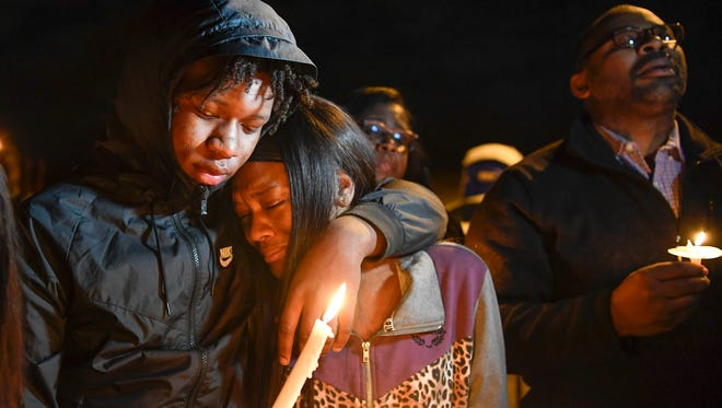 Sammy Turner comforts Dzire Cox, sister of Jeremiah Shelton-Barbee, as friends and family gather to remember him at the South Inglewood Park in Nashville, Tenn., Friday, Feb. 9, 2018.