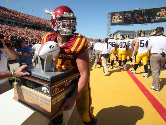 Iowa State's Tom Farniok grabs the Cy-Hawk Trophy from the Iowa sideline after the Cyclones' 44-41 triple overtime win on Saturday, Sept. 10, 2011.