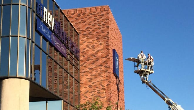 Workers install new signage at the rechristened University of Nevada, Reno Innevation Center.