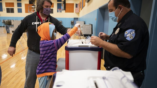 Grace Johnsen, 10, helps her father, Erik Johnsen, cast his ballot during early voting hours Saturday at Nelson Place Elementary School in Worcester.