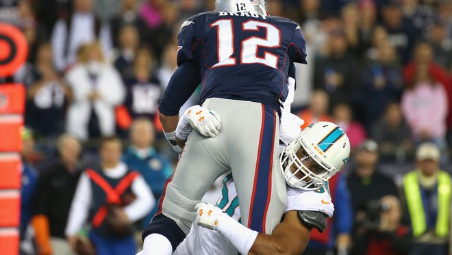 Tom Brady is tackled by Olivier Vernon.