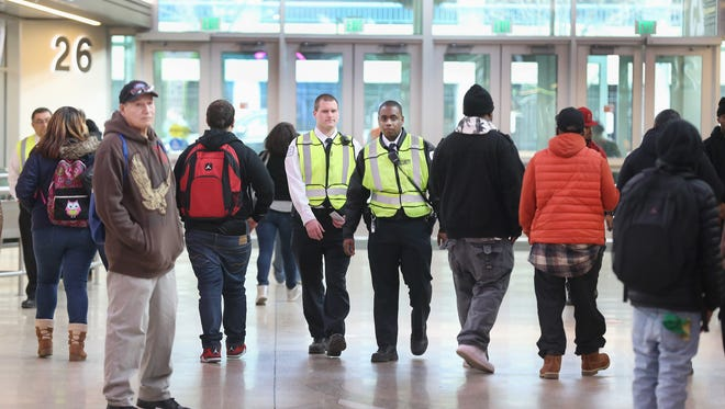 Changing bus route times to keep the volume of students more spread out and security like William Hevey, left, and Terrance Woodley, has helped to reduce violence at the Transit Center.