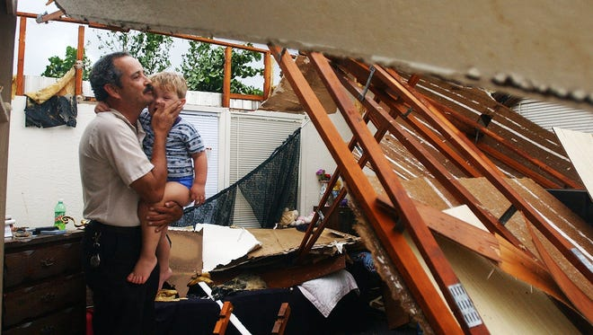 Cecil Cavenaugh hugs his grandson, Jacob,2, while taking a look through the home that Jacob and his sister live in with their grandmother in Suncoast Estates on Friday, August 14, 2004. Hurricane Charley ripped through the estates causing widespread damage.