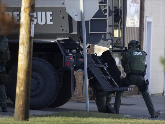 Police officers use an armored truck for cover during
