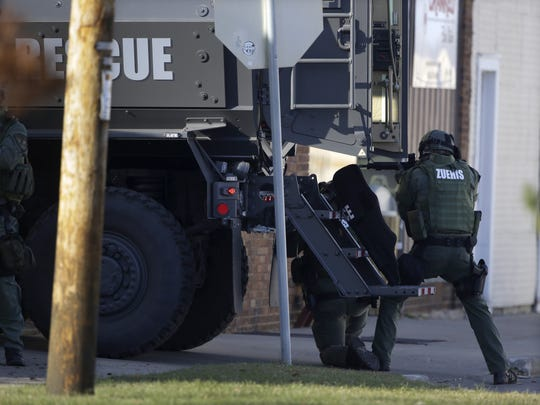 Police officers use an armored truck for cover during the Dec. 5, 2015, standoff and shooting at Eagle Nation Cycles in Neenah.